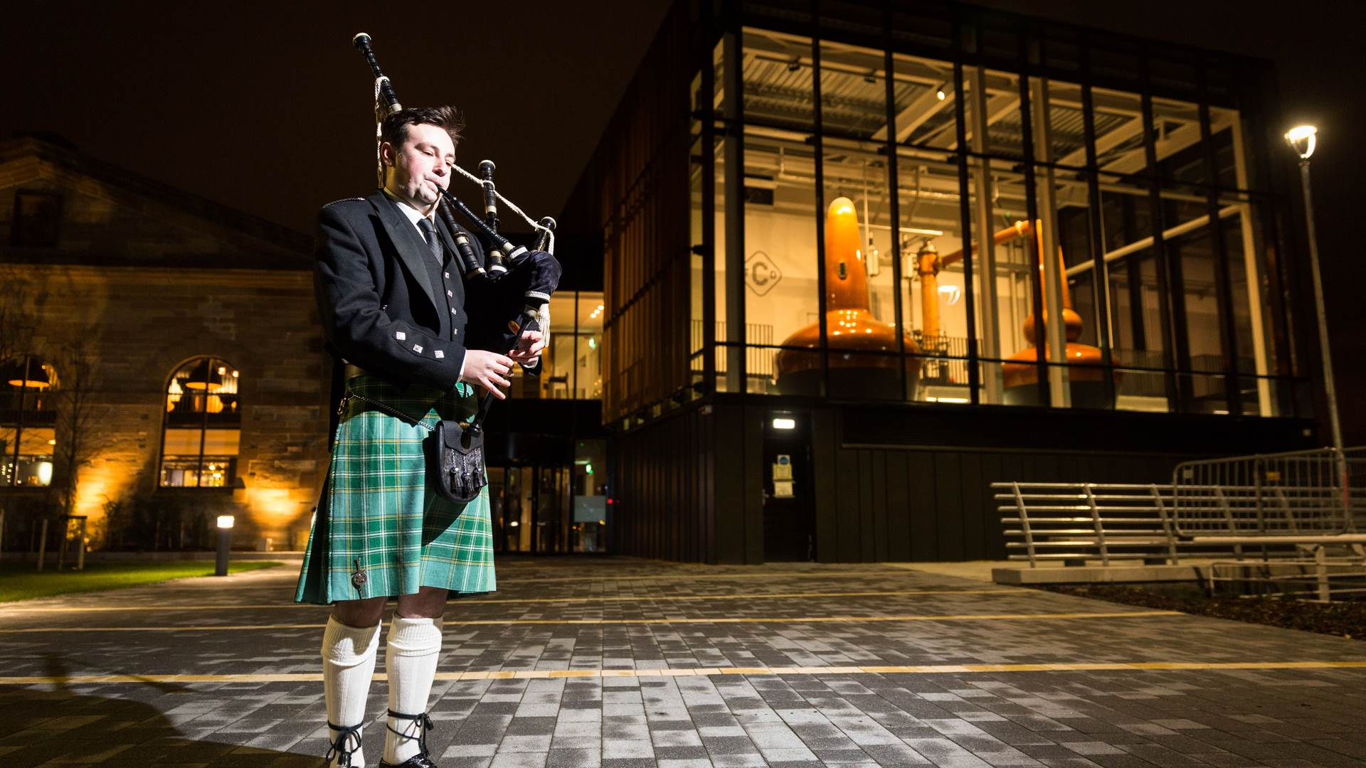 Scottish Piper outside The Clydeside Distillery welcoming evening guests