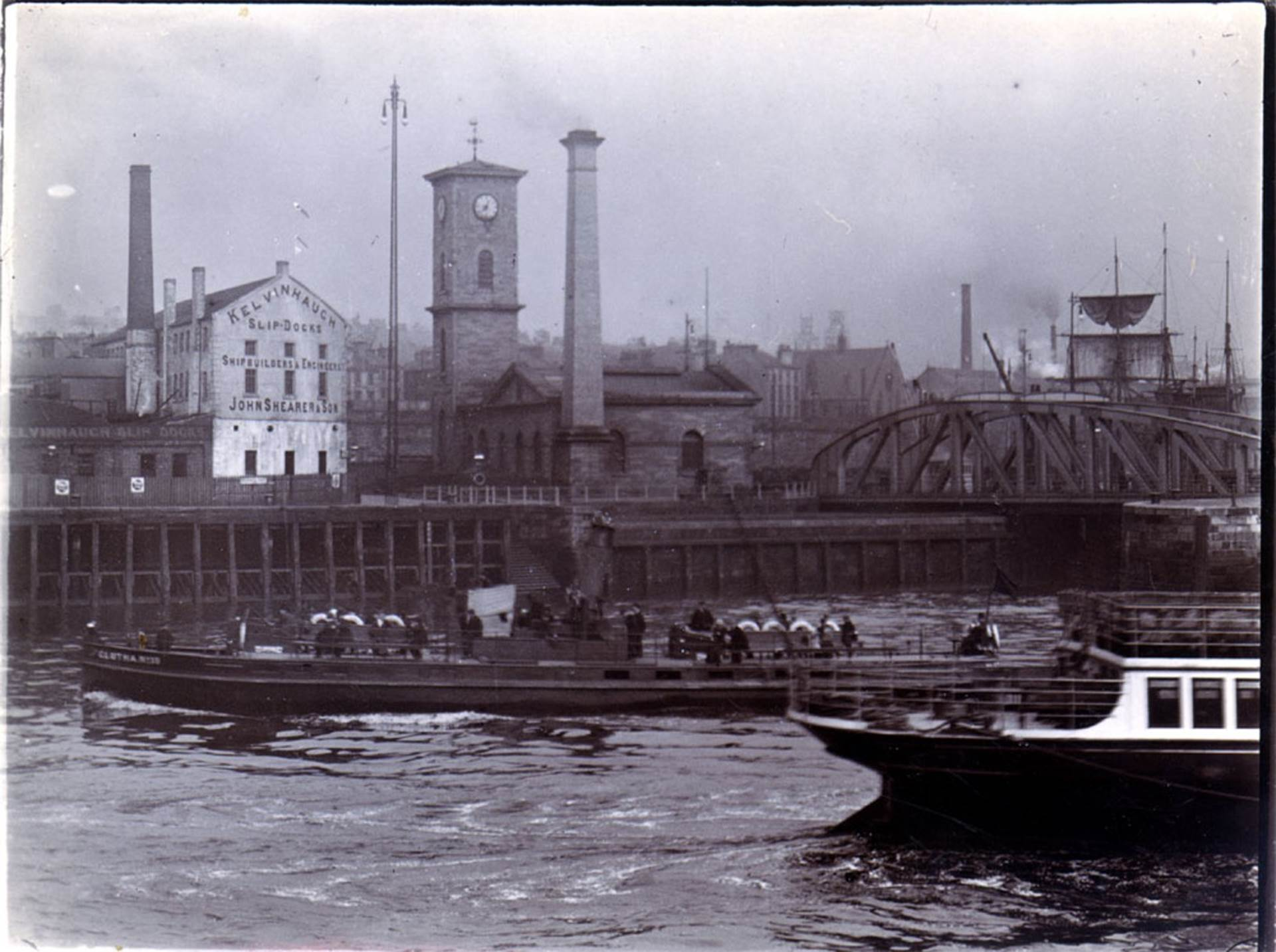20th century Clutha boats on the River Clyde passing the old Pumphouse building, which now houses the Clydeside Distillery