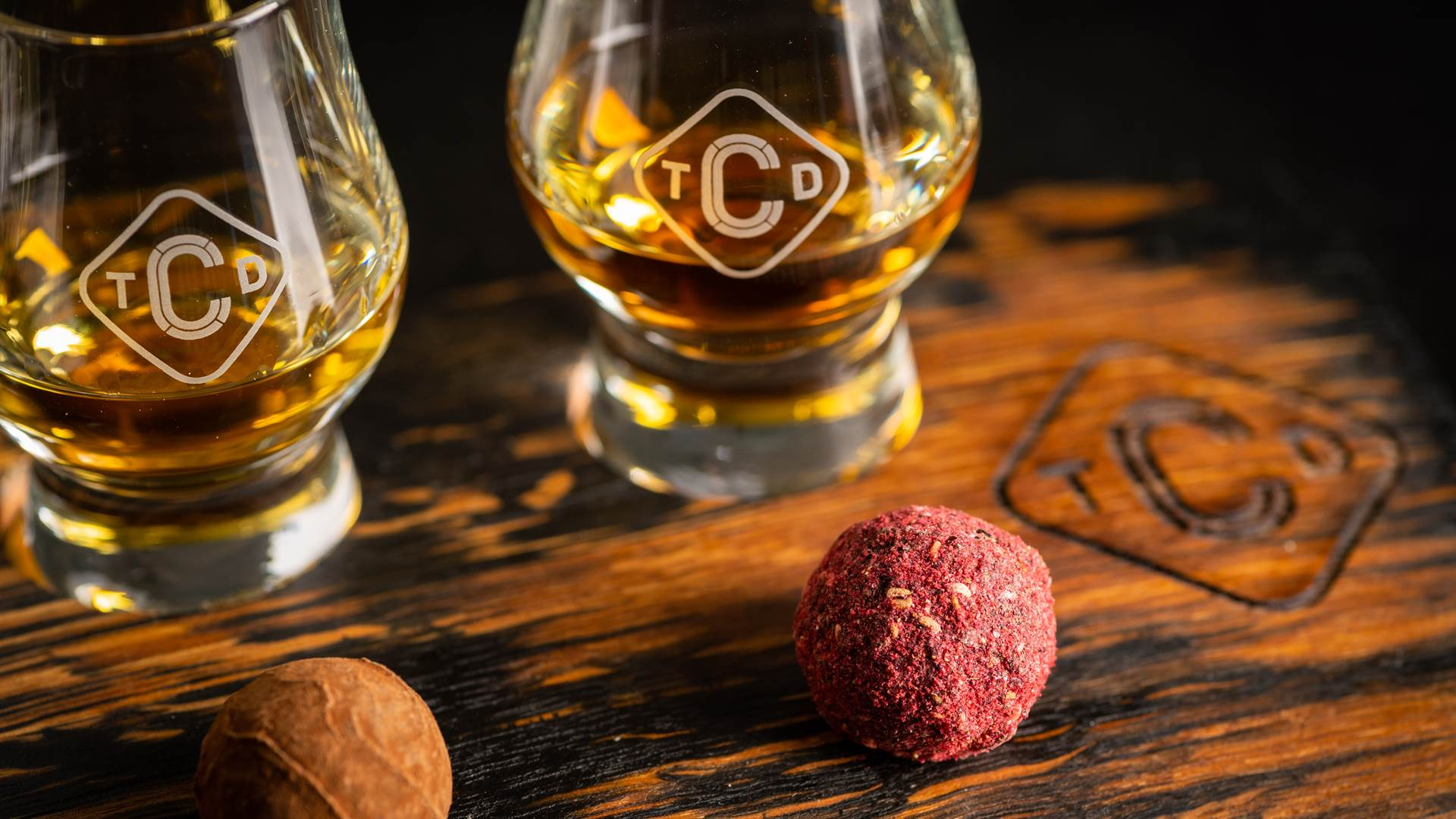 Close up of whisky & chocolate pairing, includes dram of whisky and round coated pink truffle chocolate